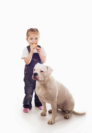 Little girl eats candy with white dog photo