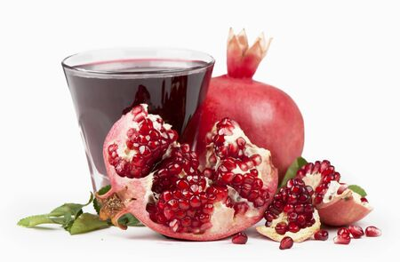 Garnet juice in a glass and pomegranate on the white photo
