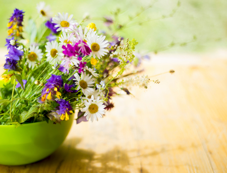 beautiful bouquet of bright wildflowers on a wooden background photo