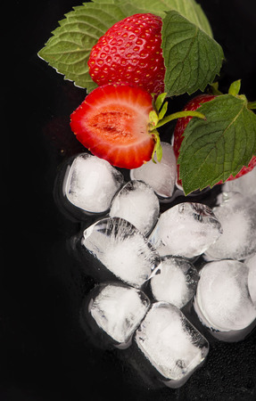 ice cubes, mint leaf,  fresh strawberry on black Stock Photo - 26415975