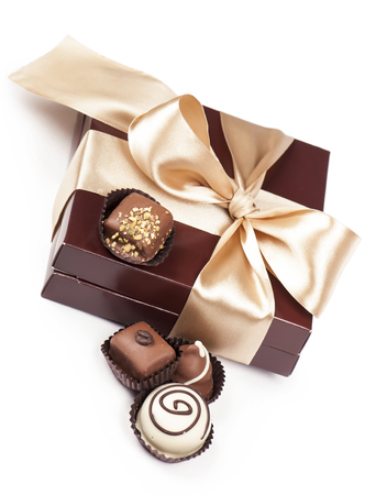 brown box with candies and golden tape isolated on the white photo
