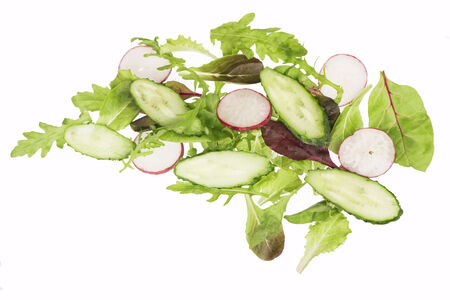 cut cucumbers, garden radish and lettuce leaves isolated on the white photo