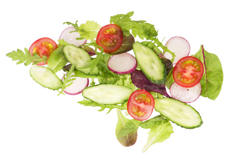 cut cucumbers, garden radish, tomatoes and lettuce leaves isolated on the white