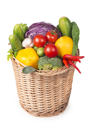 Fruits and vegetables in the basket isolated on white photo
