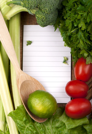 fresh vegetables on the wooden background and paper for notes photo