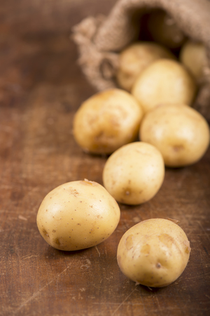 burlap bag: Raw potatoes in burlap bag  on the wooden background Stock Photo