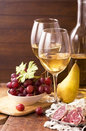 vins: Wine and grapes in vintage setting on wooden table