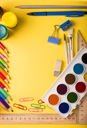 Colorful school stationery on the yellow background. 版權商用圖片