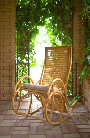 old rocking chair in the gazebo Red horse eating green grass on a field near by house and trees outdoors in the summer countryside Stockfoto
