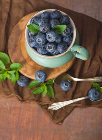 Fresh blueberry in a cup with leaves of mint