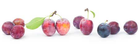 Ripe plums with leaves close up on white background
