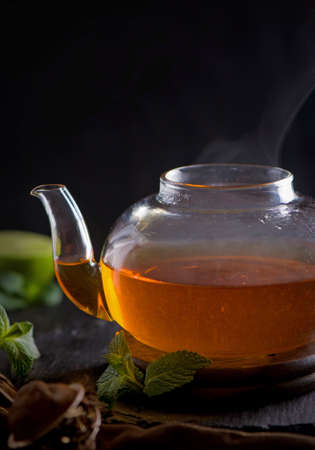 Teapot with tea surrounded with green leaves, tea ceremony, green tea in a transparent cup