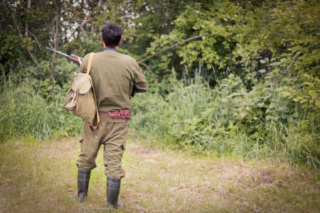 Hunter with a gun stands with his back against the background of the forest. The concept of a successful hunt, an experienced hunter. Hunting the summer season. The hunter has a rifle and a hunting uniform. Image.