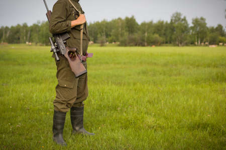 Hunter with a gun stands on the background of the forest. The concept of a successful hunt, an experienced hunter. Hunting the summer season. The hunter has a rifle and a hunting uniform. Image.