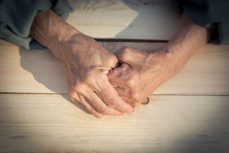 Hands of an elderly person. The concept of lonely old age, sadness and past tense, help and care older people. Image.
