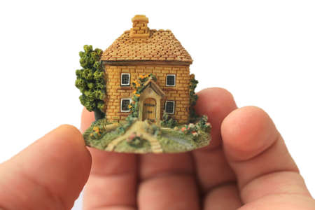 small toy house in  palm of  man photo