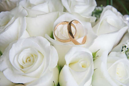 Gold wedding rings on a bouquet of white roses Stock Photo