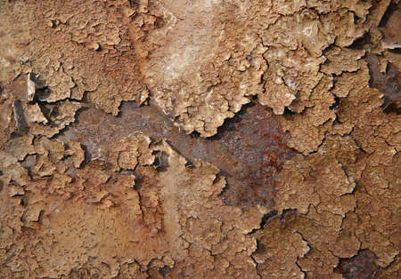 Old brown paint on a rusty metal surface. photo