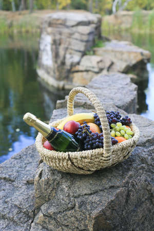 ashore: Bottle of champagne and fruit in  basket ashore