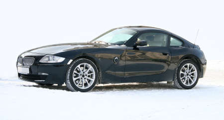 The black sports car in the winter on a white snow. Stock Photo