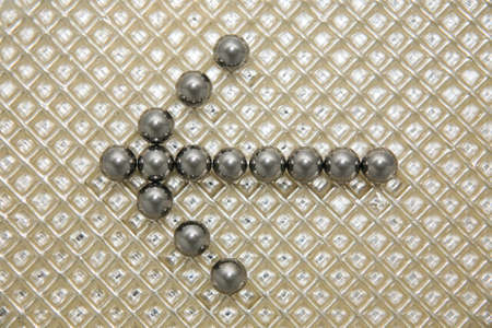 steel balls: Arrow from steel balls on a plastic textural background