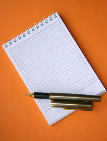 Notebook with a spiral with a place for the text and a pen on an orange background. photo