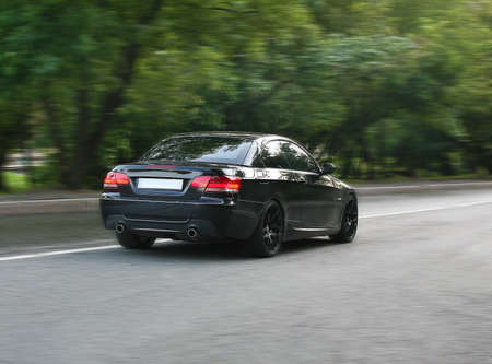 side road: beautiful modern black car going on the asphalted road Stock Photo