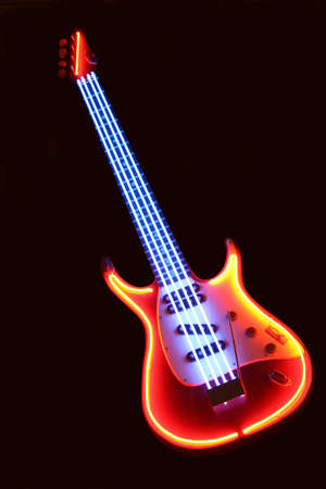 frets: Advertising model of  electronic guitar with neon illumination on  black background.