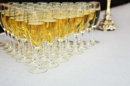 Glasses filled with sparkling wine on  long white table photo