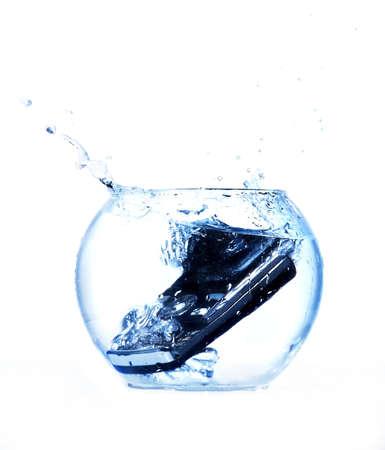 mojado: Tel�fono m�vil Negro lanzado en el acuario. Foto de archivo