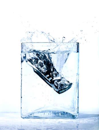 dropped: Tel�fono m�vil negro en agua Foto de archivo