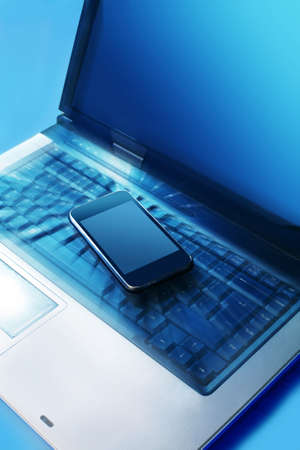 Modern mobile phone on the laptop keyboard Stock Photo - 12636149
