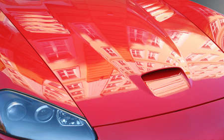 notable: Cowl of  red sports car with building reflexion