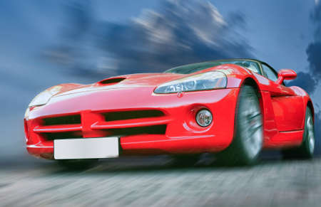 red sports car: red sports powerful car on stone blocks against  sky