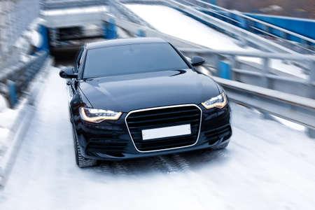 moderno automóvil negro de prestigio en muchos niveles de estacionamiento en el invierno