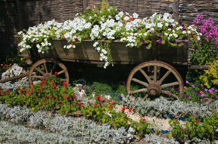 Bed  in the form of  cart filled with flowers photo