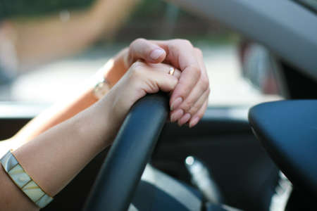 Female hands on wheel of the car close up photo