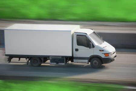 Грузовик с белым ван движется по дороге