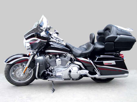 The big black brilliant motorcycle on a grey background, a side view  Stock Photo