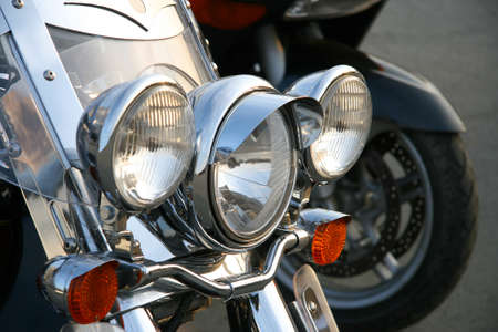 chromeplated: Three chromeplated headlights on a forward suspension bracket of a motorcycle