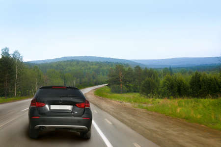 fingers on top: car goes on country road along wood Stock Photo