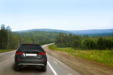 empedrado: coche salga a la carretera nacional a lo largo de la madera Foto de archivo