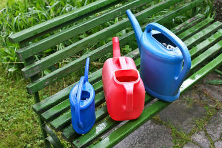 Watering cans in garden on bench against grass photo