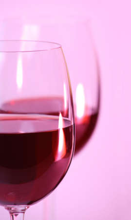 aligote: Two wine glasses with red wine on pink background closeup Stock Photo