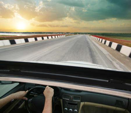 Машина едет по дороге в страну на закате