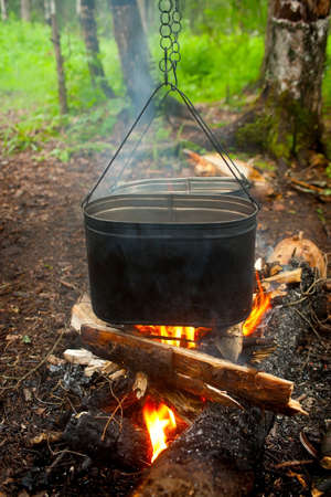 Cooking on fire in kettles on nature photo