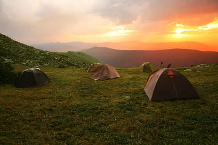 Mountain landscape with sunset and tents on glade Stock Photo - 14045410