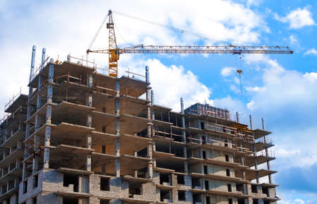 crane over new high-rise under construction residential building Stock Photo