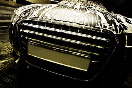 dark prestigious car on car wash Stock Photo