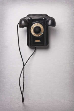 rotary dial telephone: Old black rotational phone on wall Stock Photo